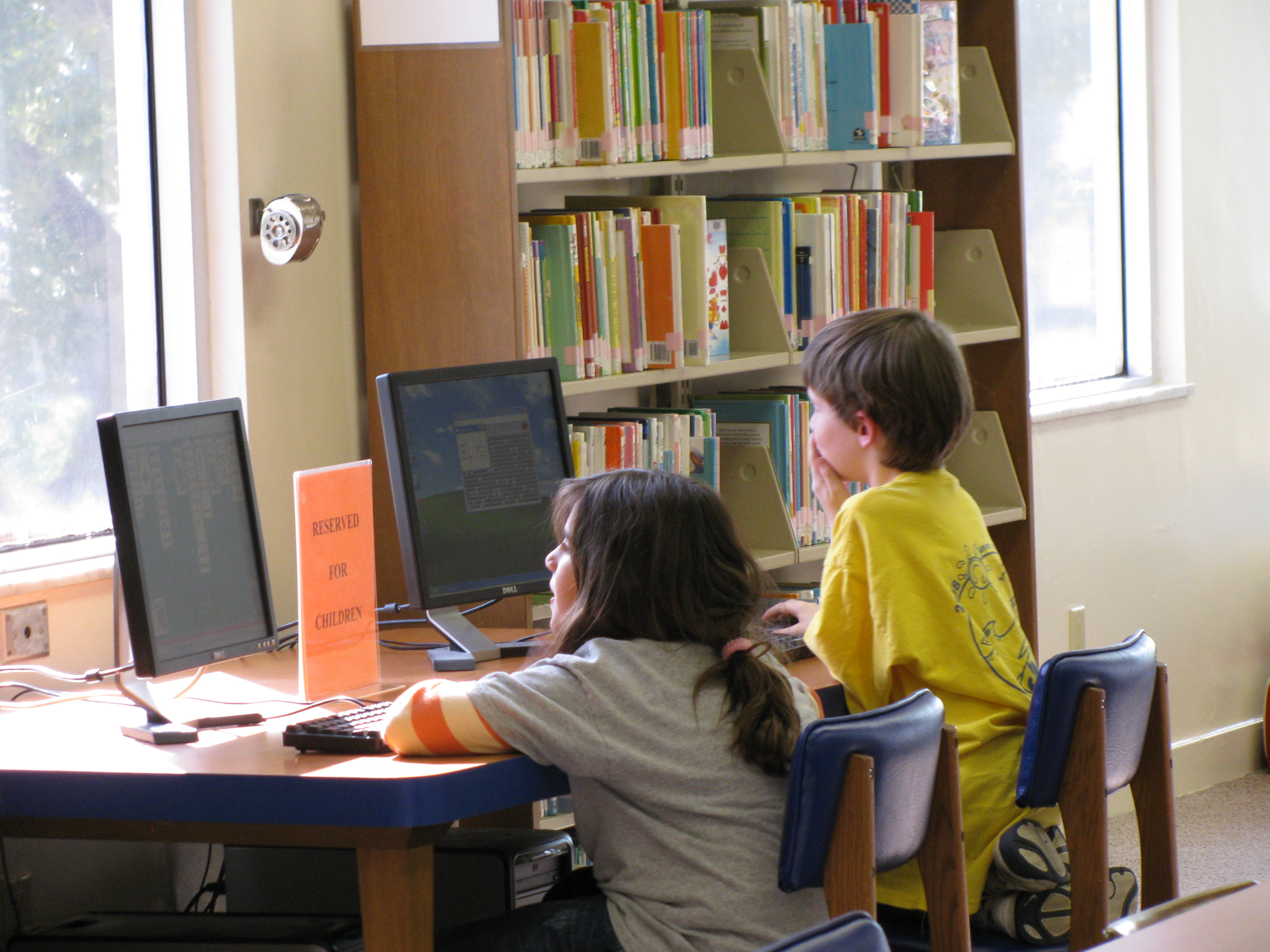 Children sitting at wooden desk on computers